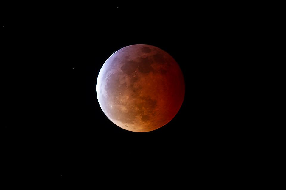 a lunar eclipse, where the moon turns red and looks shadowed