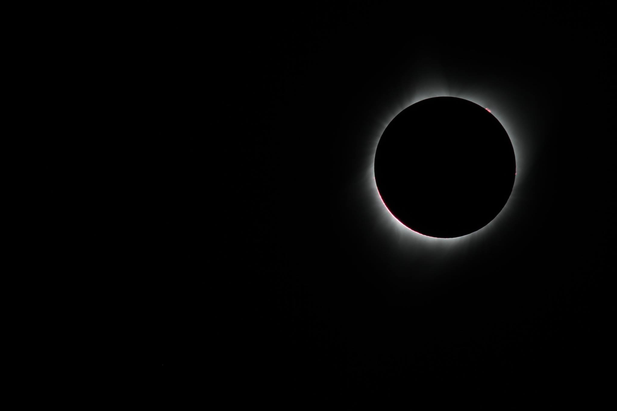 a solar eclipse where the moon has completely blotted out the sun to black except for a faint white glow at the edge and a small reddish-pink burst at the top right
